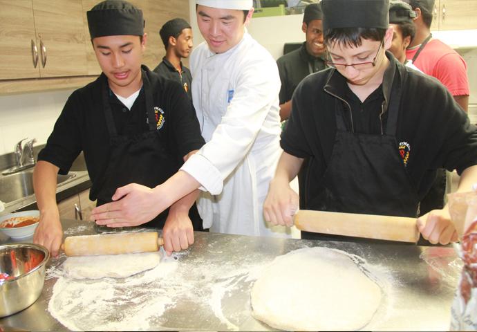 Des participants au programme Guys Can Cook roulent de la pâte à pizza avec un étudiant-chef du collège George Brown, au CSC Four Villages, en 2015.